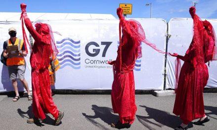 Διαδηλωτές με μάσκες και κόκκινα ρούχα ζητούν άμεση δράση των ηγετών για το Κλίμα